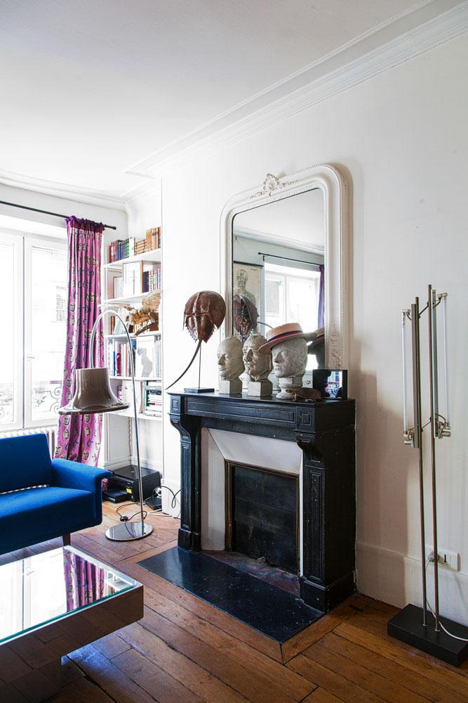 Salon Cheminée Sculptures Miroir ancien Bibliothèque Livres Canapé bleu Appartement Créatrice DA/DA Diane Ducasse