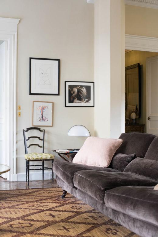 Canapé en velours et cadres photo dans le salon d'Alessandro Moriconi et Antoni Calmon à Paris