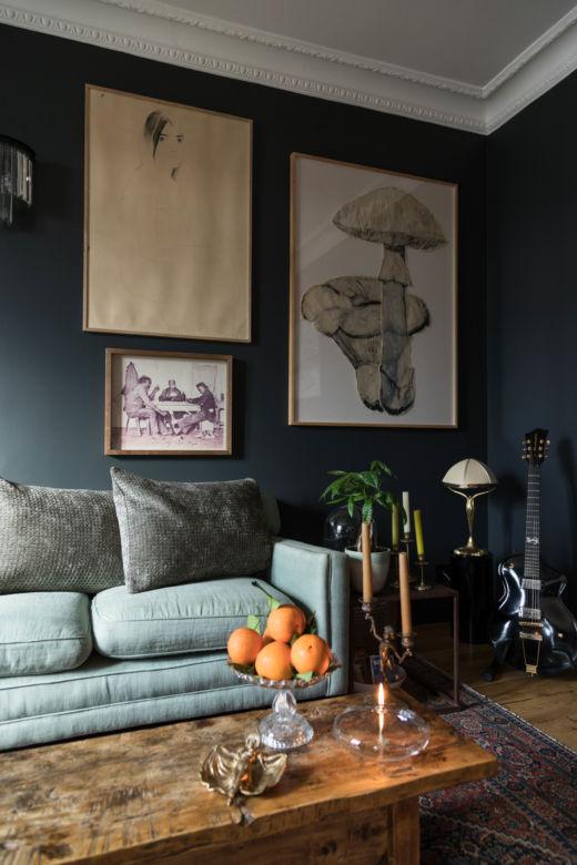 Canapé en velours vert d'eau, table basse en bois et affiches chez Keren Ann à Paris