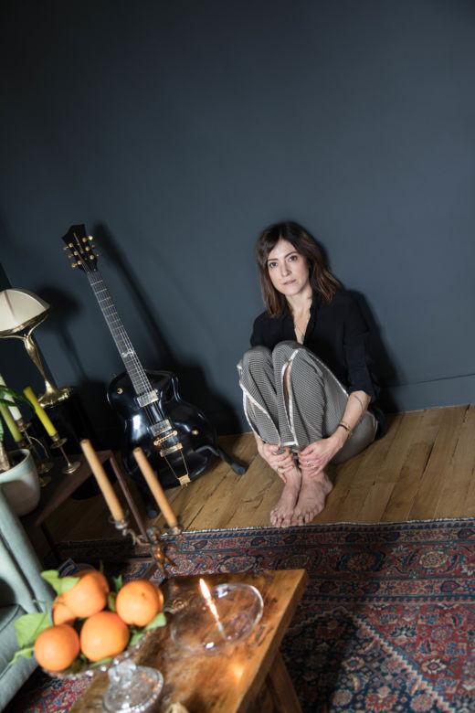 Keren Ann à côté de sa guitare et de sa table basse dans son salon à Paris