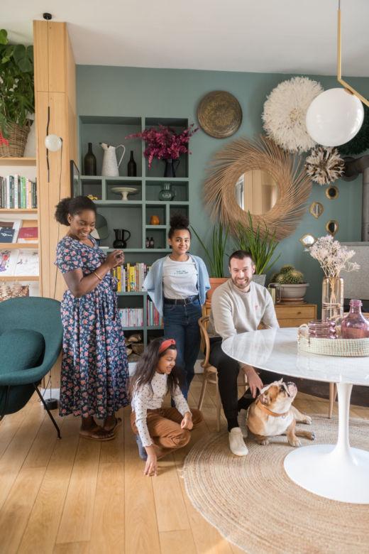 La famille Marlin dans leur salon couleur vert d'eau avec table en marbre et miroirs en rotin à Paris
