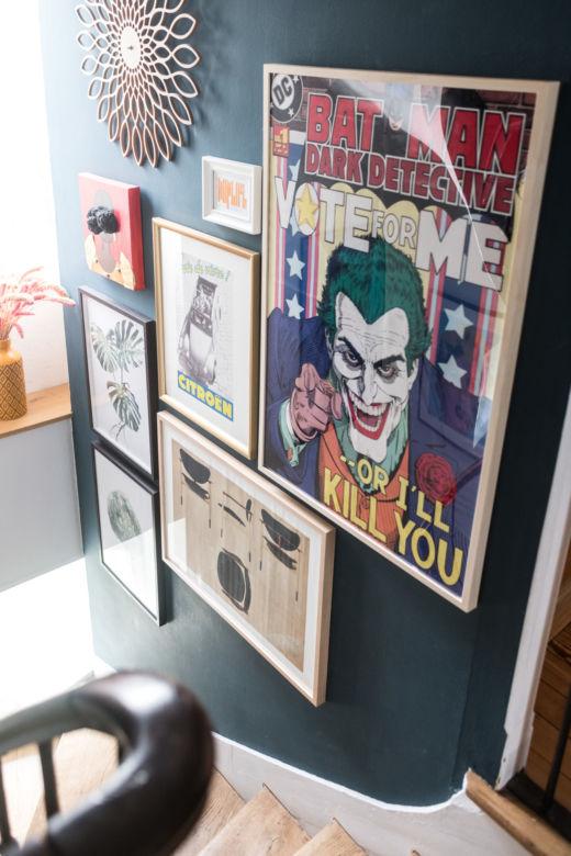 Escaliers avec peinture noire, miroir en rotin et affiche vintage Joker chez Babeth et William Marlin à Paris