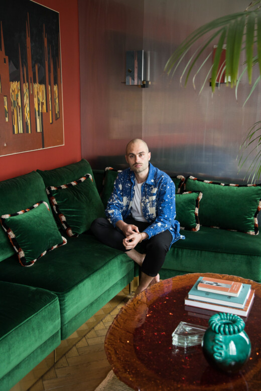 Hugo Toro sur son canapé en velours vert dans son salon à Paris